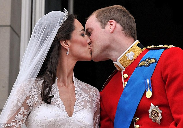 The bride and groom embrace on the balcony of Buckingham Palace